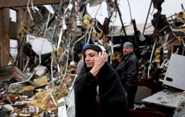 Pam Parker sifts through debris while looking for any personal belongings in the area where she was sitting at her desk when a tornado struck the Daiki plant, a metal fabrication company where she works, in Adairsville, Ga. (AP Photo/David Goldman)